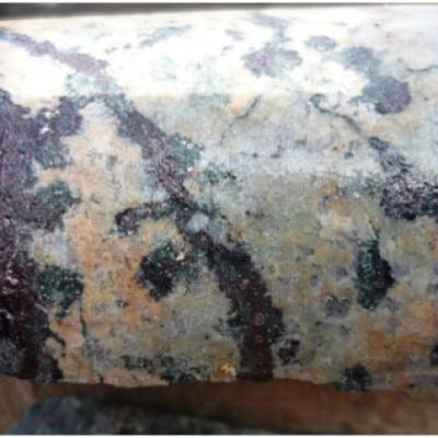 Bornite in specs and veinlets in muscovite-sericite veins Zone 2